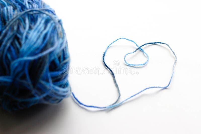 Ein Ball des blauen Wollgarns Thread breitete die Form eines Herzens aus stockfotografie