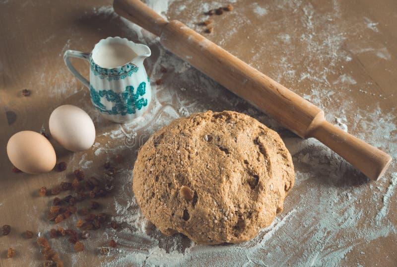 Ein Ball des Getreidespeicherbrotteigs mit Abstauben des Mehls und des Nudelholzes, der Eier und der Milch auf Holztisch in einem stockbild