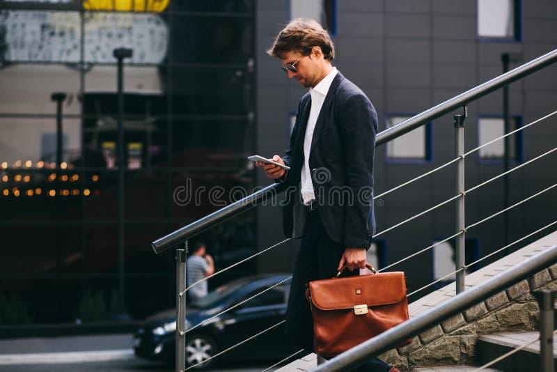 Ein Banker in einem stilvollen Anzug mit Handy geht die Treppe hinunter lizenzfreie stockfotografie