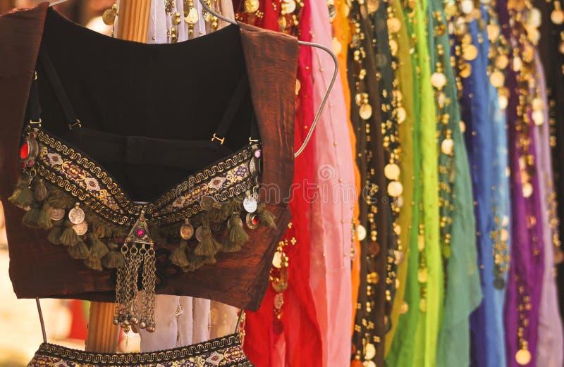 Ein Bauch-Tanzen-Kostüm und bunten Röcke lizenzfreie stockbilder