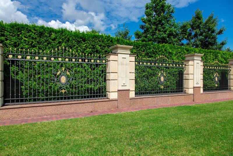 Ein bearbeiteter Zaun des Eisens mit Hauptsteinsäulen stockbild