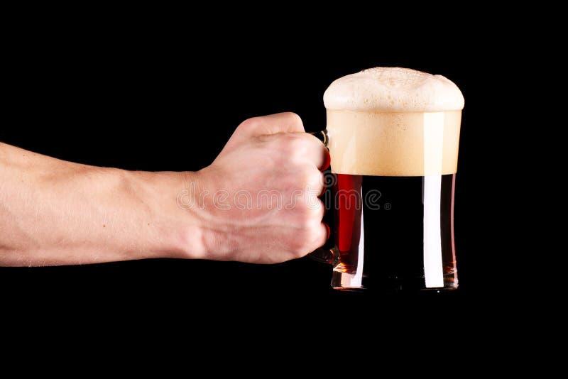 Ein Becher schwarzes Bier in der Kerlhand Lokalisierter Hintergrund lizenzfreies stockfoto