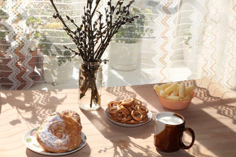 Ein Becher von Milch, von Schale Mais und von Kuchen auf einer sonnigen Tabelle, ein Blumenstrauß von Frühlingsblumen für Stimmun lizenzfreie stockfotografie