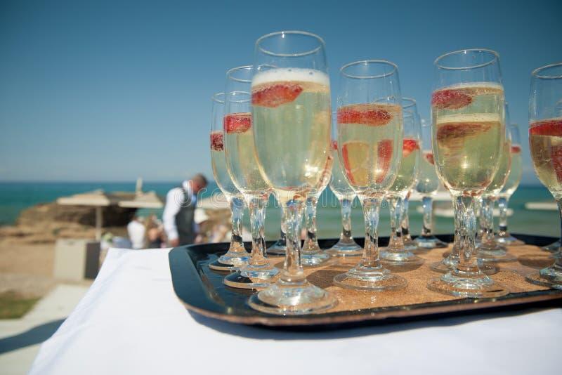 Ein Behälter des Sektes mit Erdbeeren durch den Strand, heiratend lizenzfreies stockfoto
