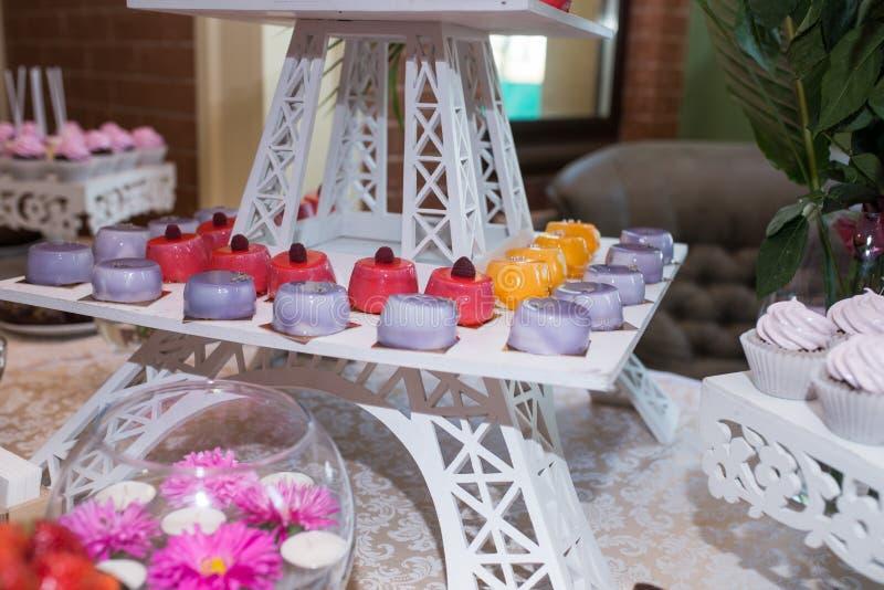 Ein Behälter mit Rosa, Orange und lila kleinen Kuchen Schokoriegel Viele Bonbons am Hochzeitsbankett lizenzfreies stockfoto