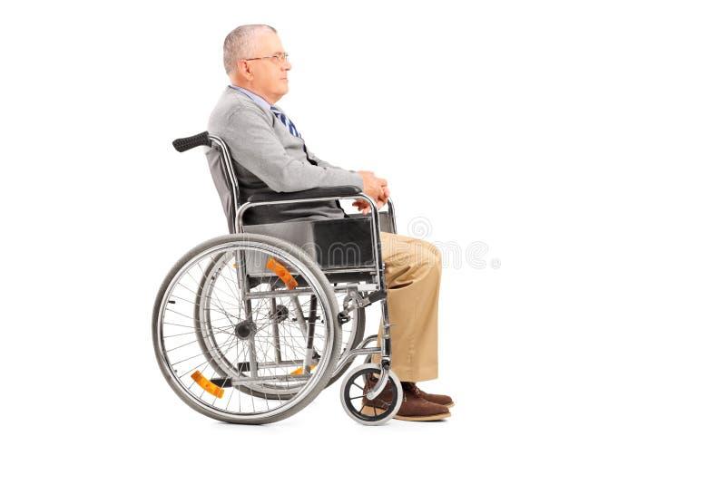 Ein behinderter älterer Herr, der in einem Rollstuhl aufwirft stockfotografie