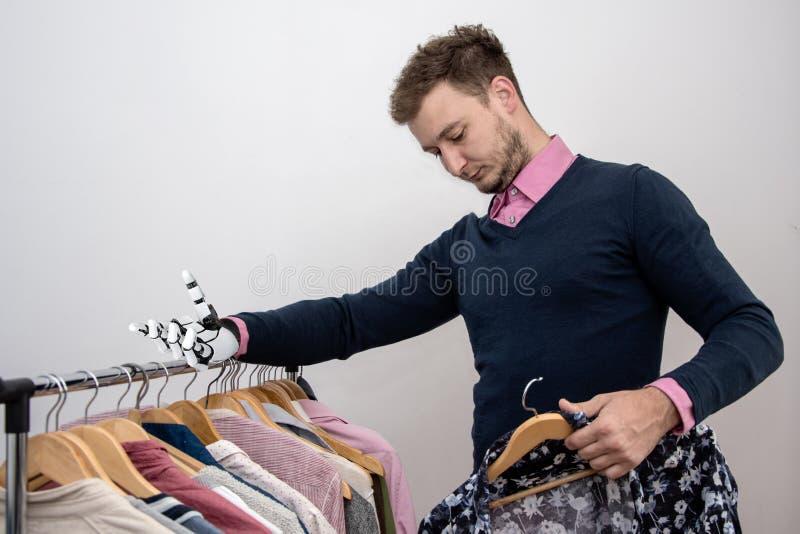 Ein behinderter Mann mit Roboterarmprothese wählt Kleidung Konzept: Anpassung behinderter Menschen an den Alltag, menschlicher Ro lizenzfreies stockfoto
