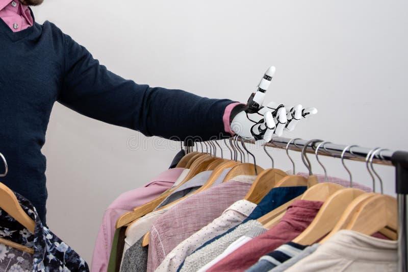 Ein behinderter Mann mit Roboterarmprothese wählt Kleidung Konzept: Anpassung behinderter Menschen an den Alltag lizenzfreies stockbild