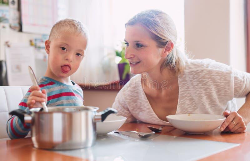 Ein behindertes Down-Syndrom Kind mit seiner Mutter, die zuhause das Mittagessen isst lizenzfreies stockfoto