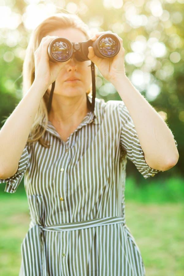 Ein Beobachter benutzt die schwarzen Ferngläser im Freien stockfoto