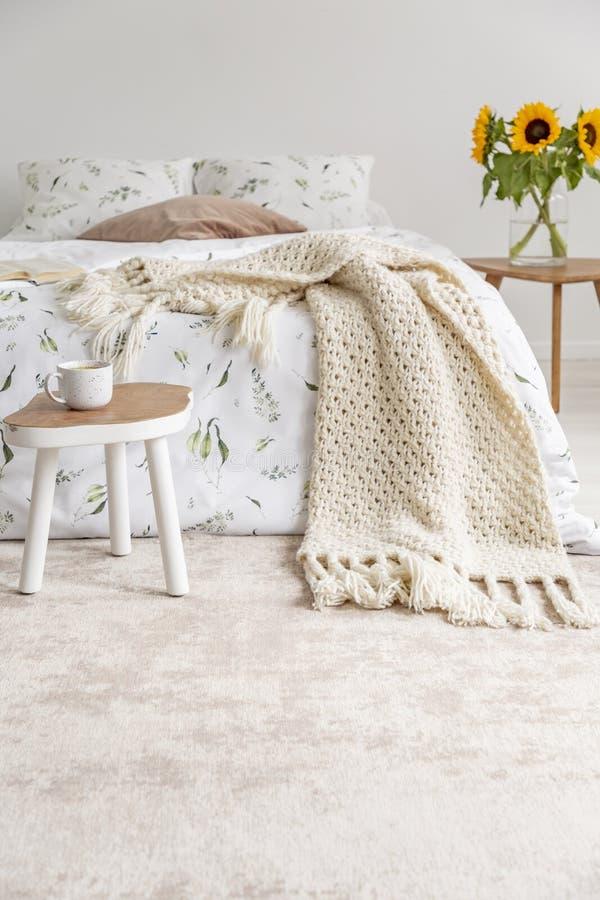 Ein bequemes Bett kleidete im weißen Leinen der Biobaumwolle mit grünem Druck in einem natürlichen Schlafzimmerinnenraum an lizenzfreies stockbild