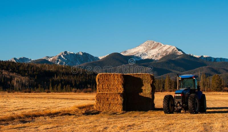 Ein Berg steigt über ein Traktor- und Heufeld lizenzfreie stockfotos