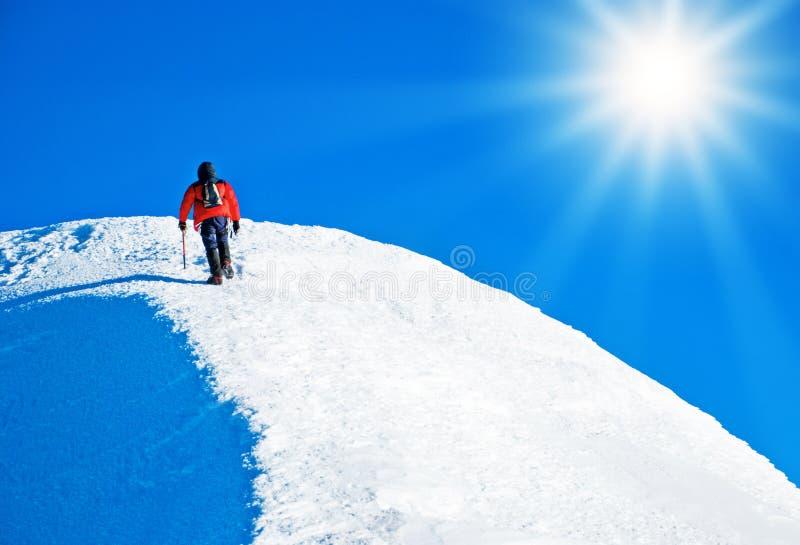 Ein Bergsteiger, der den Gipfel erreicht stockfoto