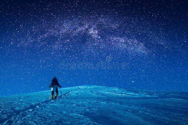 Ein Bergsteiger klettert oben eine schneebedeckte Steigung nachts lizenzfreie stockbilder