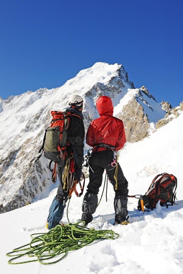 Ein Bergsteiger zwei, der den Gipfel erreicht stockbild