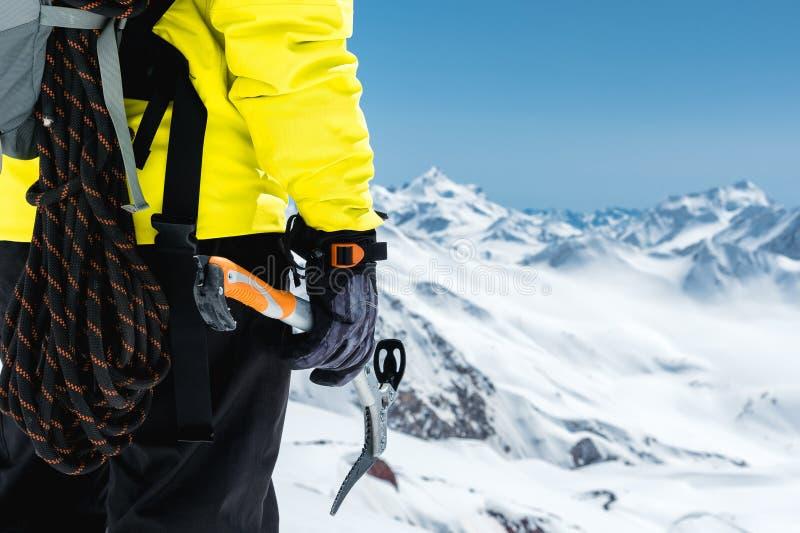 Ein Bergsteigermann hält eine Eisaxt hoch in den Bergen, die mit Schnee bedeckt werden Nahaufnahme von hinten extremes im Freien  lizenzfreies stockbild