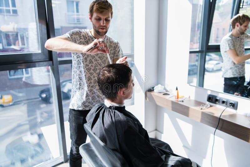Ein Berufsherrenfriseur mit einem Kamm und Scheren in seiner Hand, die das nass schwarze und kurze Haar des Mannes in a anredet stockbild