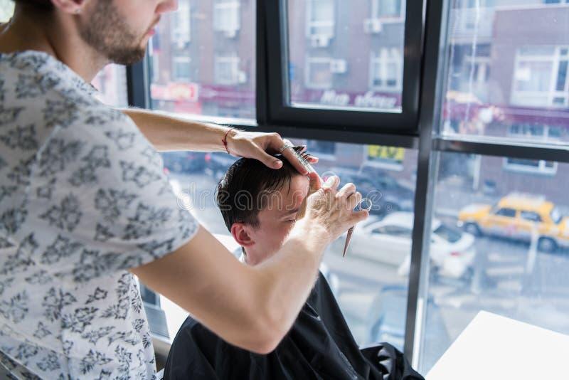 Ein Berufsherrenfriseur mit einem Kamm und Scheren in seiner Hand, die das nass schwarze und kurze Haar des Mannes in a anredet stockfoto