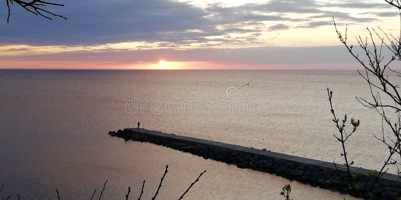 Ein Besorgnis erregender und schöner Meerblick Das herbstliche dunkle Meer Auf einem Steinpier ein Schattenbild eines Mannes Symb lizenzfreie stockbilder