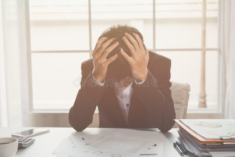 Ein betonter heraus Geschäftsmann hält seinen Kopf in der Verzweiflung stockfoto