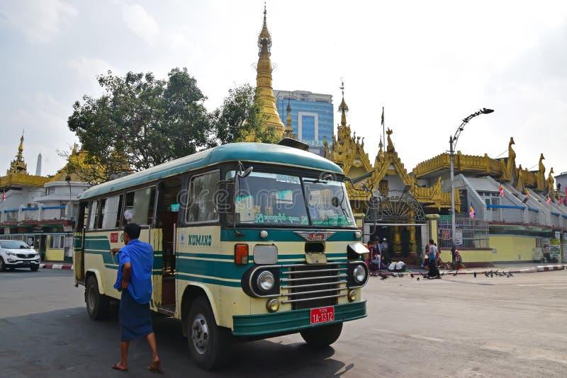 Ein beweglicher Bus und ein Fußgänger vor Sule Pagoda in im Stadtzentrum gelegenem Rangun, Myanmar lizenzfreie stockfotos
