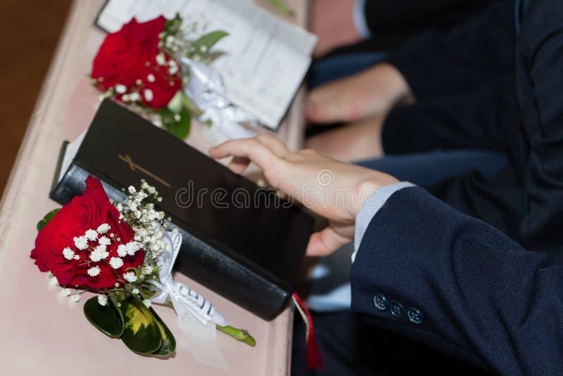 Ein Bild der heiligen Bibel mit roten Rosen in der Kirche stockbilder