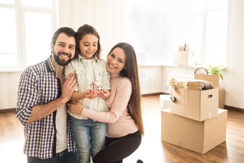 Ein Bild des Vaters, der Mutter und ihres Kindes, die in einem hellen Raum stehen Eltern umarmen ihr Kind und lächeln während lizenzfreies stockbild