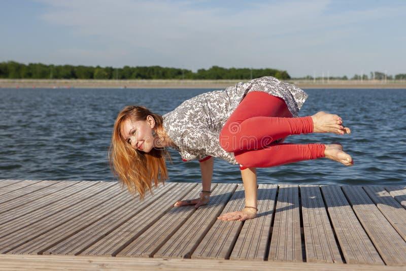 Ein Bild einer h?bschen Frau, die Yoga am See tut stockbilder