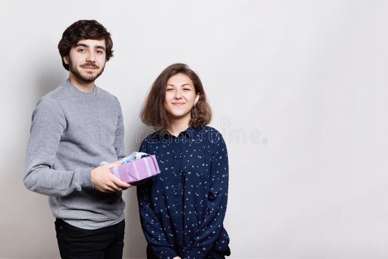 Ein Bild eines frohen Paares, das nah an einander über dem weißen Hintergrund hält ein Geschenk steht Gefühle annehmen und teilen stockbild