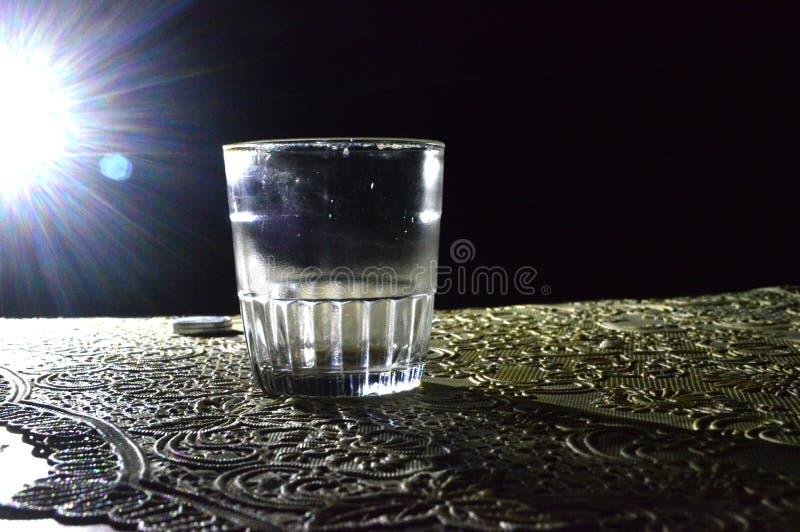 Ein Bild eines Glases in der Dunkelheit mit einem wenig Licht stockbild