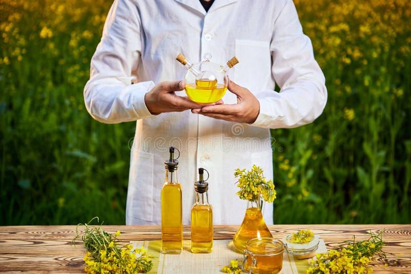 Ein Biologe oder ein Agronom des jungen Mannes überprüft die Qualität des Rapsöls auf einem Rapsfeld Agrargesch?ftskonzept stockfoto