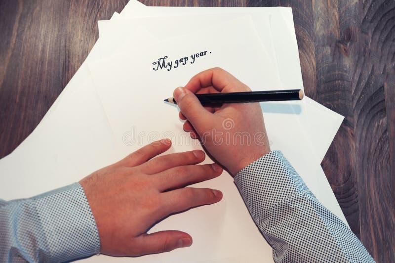 Ein Blatt Papier vor einem Mann mit den Wörtern: Mein Abstandsjahr Planung von Angelegenheiten für das Jahr Das Konzept getont lizenzfreie stockfotos