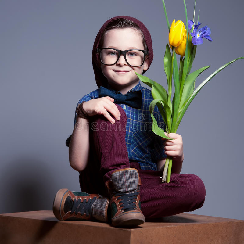 Ein blauäugiges Kind mit Gläsern Ein Junge sitzt mit einem Lächeln auf Gesicht stockbild