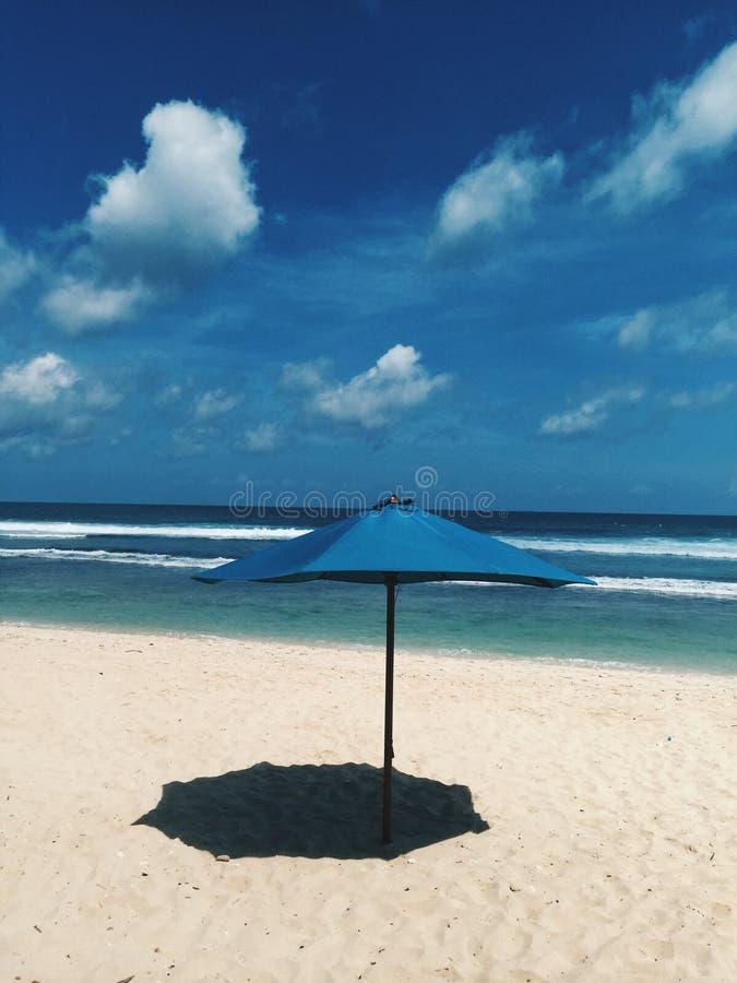 Ein blauer Strandsonnenregenschirm Schatten auf dem Sand machen lizenzfreie stockfotos