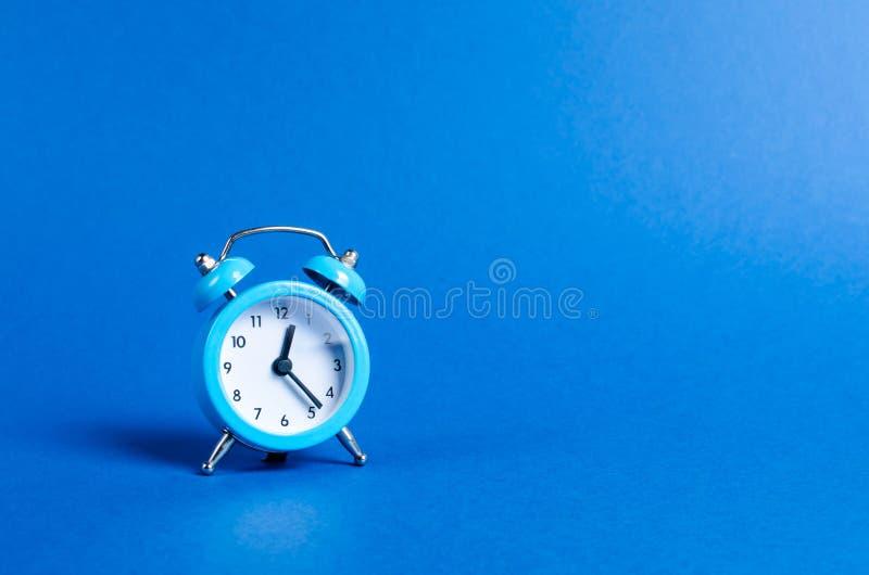 Ein blauer Wecker auf einem blauen Hintergrund Begrenztes Angebot und im Laufe der Zeit Planung und Disziplin Warten auf eine Sit lizenzfreie stockbilder