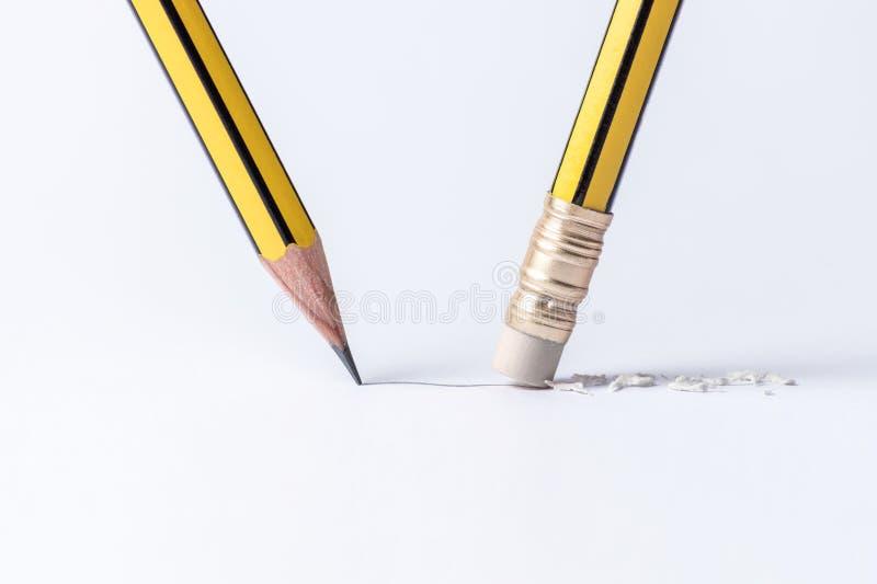 Ein Bleistift zeichnet eine Linie auf Papier und ein Bleistift mit einem Radiergummi entfernt einen Streifen stockfotos