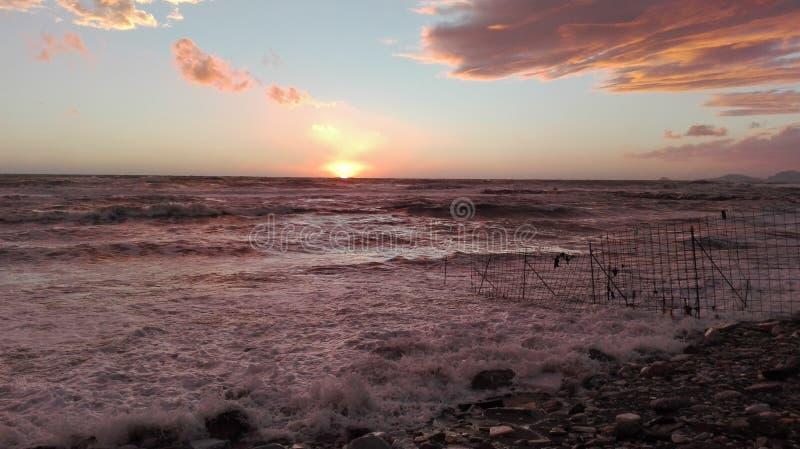 Ein Blick des Strandes bei Sonnenuntergang, ein magischer Moment, in dem alles mit hellen Farben gefärbt wird die Wolken gestalte stockbilder
