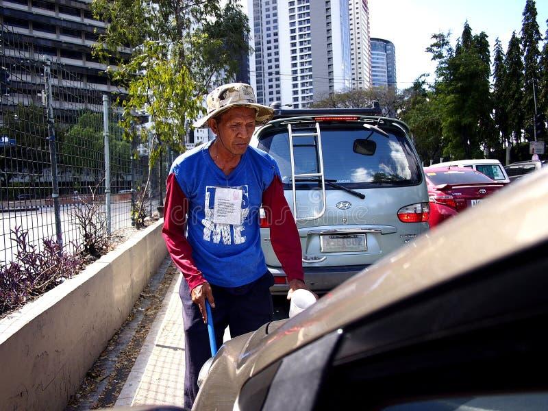 Ein blinder Bettler, der um Almosen unter Kraftfahrern an einer Hauptstraße in Pasig-Stadt, Philippinen bittet stockbild