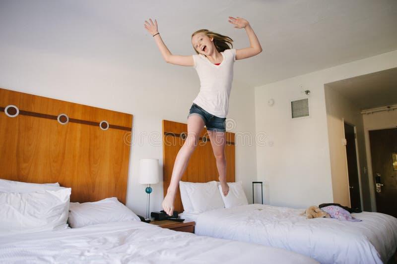 Ein blondes jugendlich Mädchen, das auf Betten in einem Hotel springt. lizenzfreie stockfotos