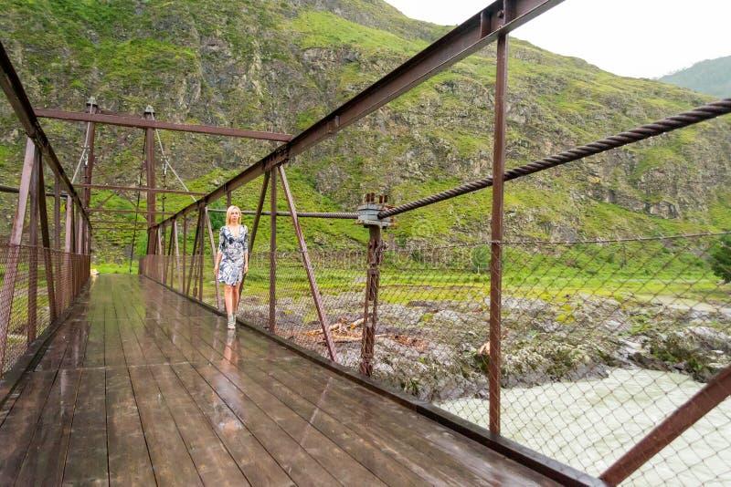 Ein blondes Mädchen in einem kurzen Farbkleid, lange Beine in den Schuhen tritt O lizenzfreie stockbilder