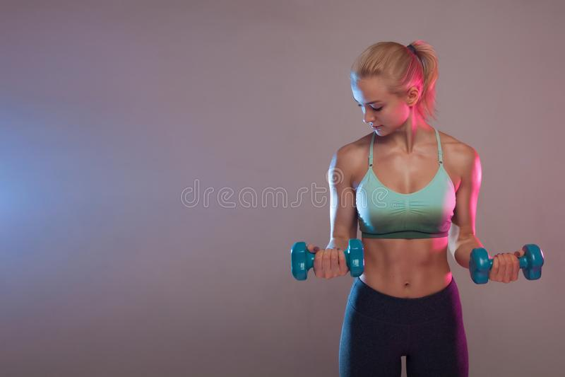 Ein blondes sportliches Mädchen hält einen Dummkopf in ihren Händen, rüttelt ein muskulöses Gegen einen dunklen Hintergrund lizenzfreies stockbild