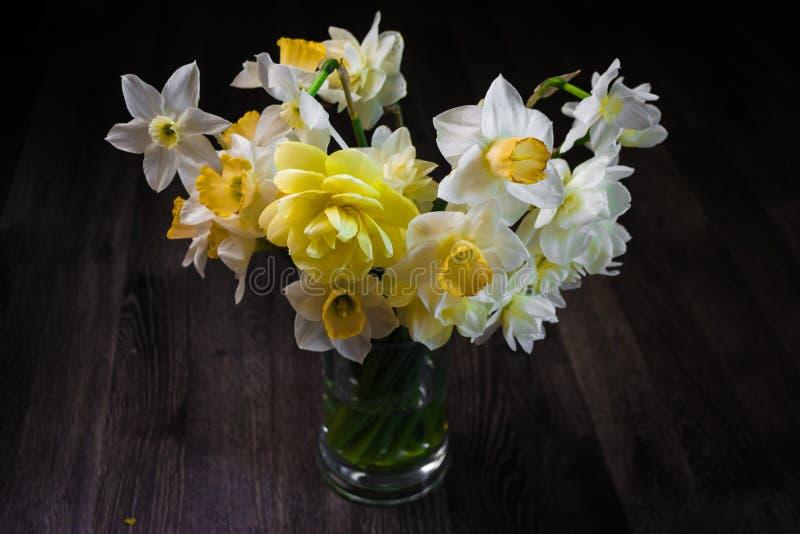 Ein Blumenstrauß von Blumen auf einem dunklen hölzernen Hintergrund Wei?e Narzisse in einem Vase Platz f?r Ihren Text Beschneidun stockbilder