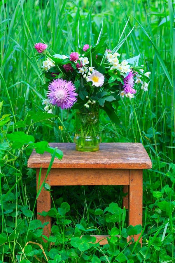 Ein Blumenstrauß von Blumen des Klees, der Kornblumen und des Jasmins in einem Glasvase auf einem alten hölzernen Schemel unter d lizenzfreies stockbild