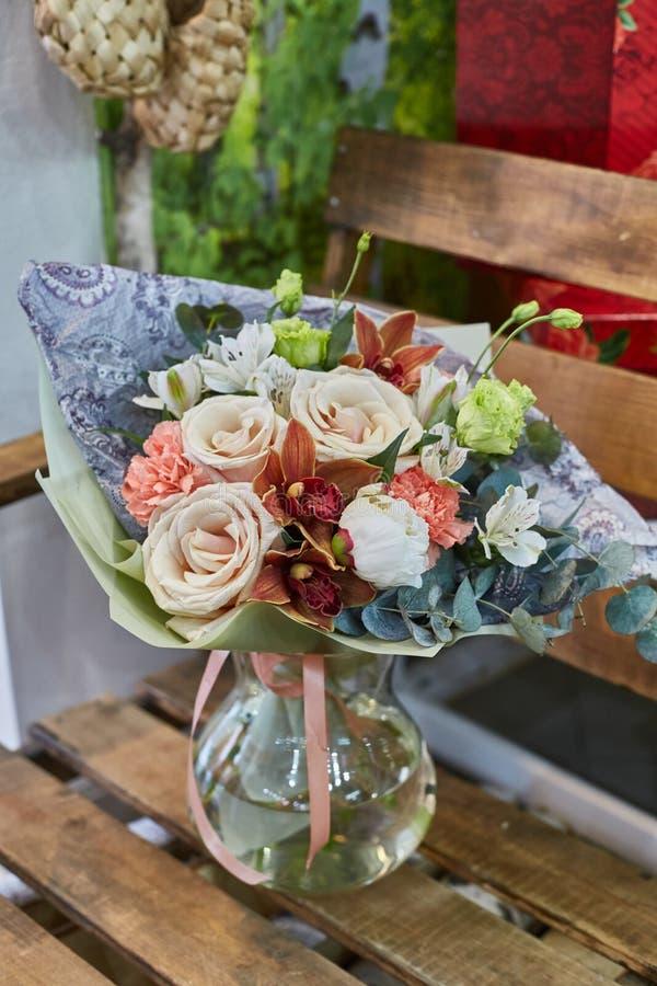 Ein Blumenstrauß von Blumen in einem Glasvase auf einem Hintergrund von hölzernen Brettern in einer warmen braunen Skala lizenzfreies stockfoto