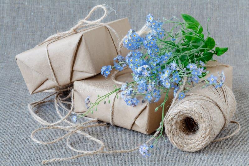 Ein Blumenstrauß von Blumenvergissmeinnichten mit Geschenk lizenzfreie stockbilder