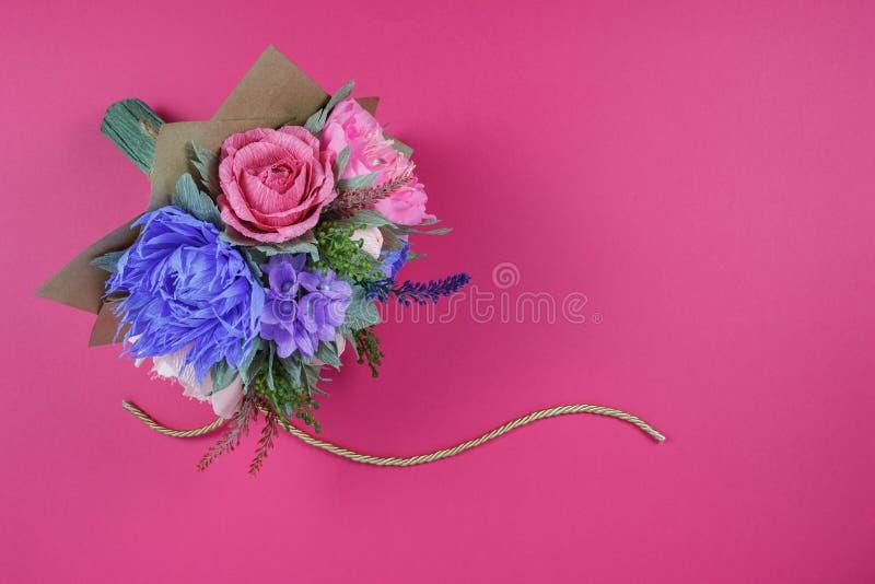 Ein Blumenstrauß von bunten Papierblumen auf einem magentaroten Hintergrund als Hintergrund für eine Postkarte, ein Einladungssch stockbilder