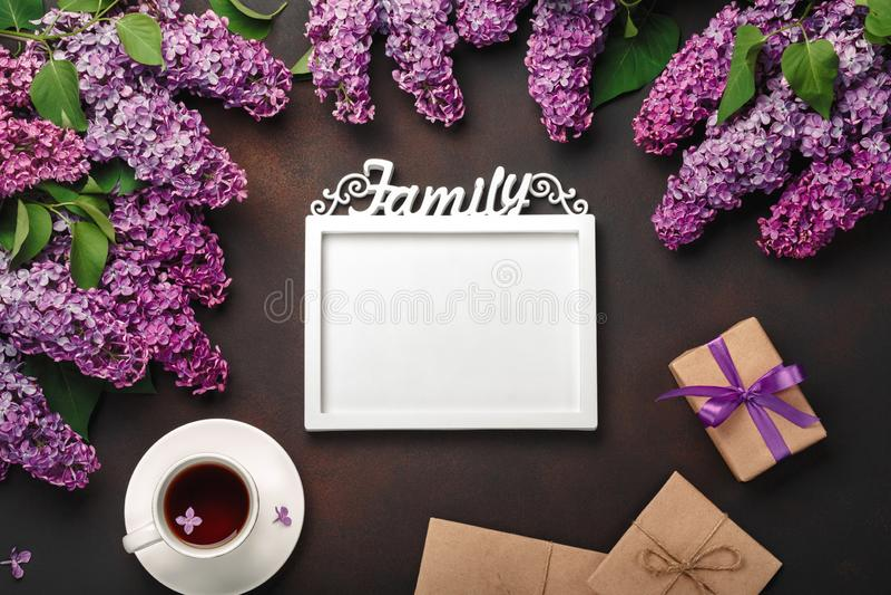 Ein Blumenstrauß von Fliedern mit Tasse Tee, ein weißer Rahmen für Aufschrift, Geschenkbox, Handwerksumschlag, eine Liebesanmerku stockfotografie