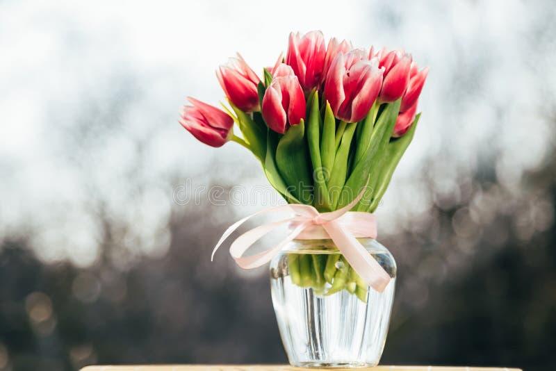 Ein Blumenstrauß von frischen rosa Tulpen in einem Glasvase draußen Beschneidungspfad eingeschlossen lizenzfreie stockfotos