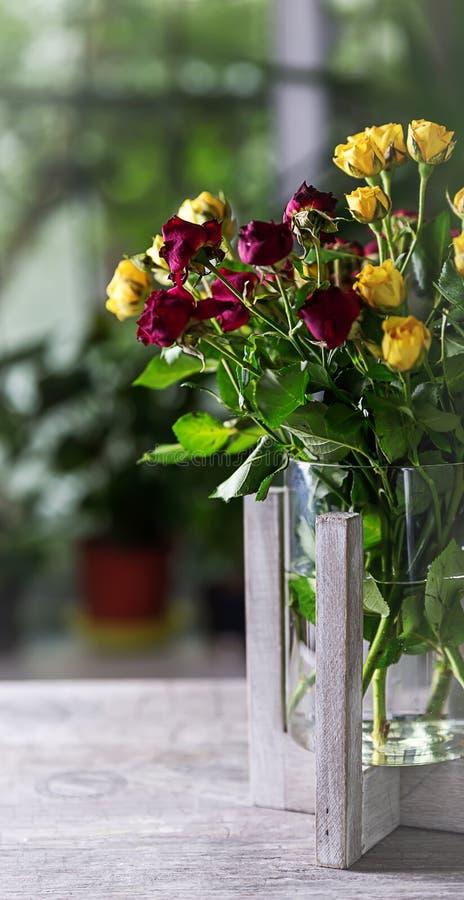 Ein Blumenstrauß von roten und gelben Rosen auf einer Tabelle in einem Vase lizenzfreie stockfotografie
