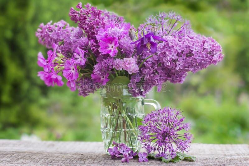 Ein Blumenstrauß von schönen Blumen der Flieder auf einem Hintergrund des Grüns lizenzfreie stockfotos